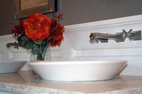 A vessel sink rests on top of or is slightly submerged in the vanity.