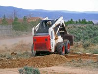 A skid loader can clear and grade land.