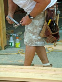 A carpenter holds a rafter square.