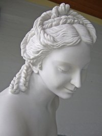 An elaborate hairstyle adorns this statue of an aristocratic Grecian woman.