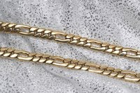 Figaro chains feature oblong links interspersed along the length of the chain.