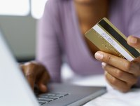 A close-up of a woman making a purchase online with a credit card.