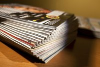 A stack of magazines partially in shadow on a table.