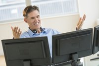 Businessman working on two desktops