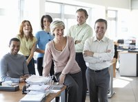 A happy group of employees at an office desk.