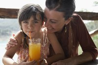 Girl uses a straw to drink a glass of orange juice next to her mother.