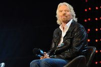 Successful entrepreneur Richard Branson sitting on stage.