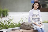 Potential university student sitting on outdoor bench.