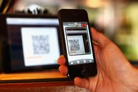 A smartphone scans a QR code posted in a shop
