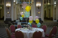 A table is decorated with party balloons in a hotel.