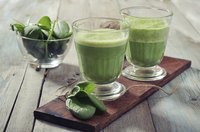 A bowl of spinach and two spinach smoothies.