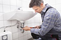 Man working on sink drain.