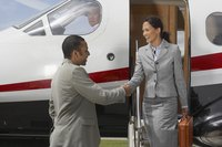 Woman shaking hands with businessman while disembarking from jet.