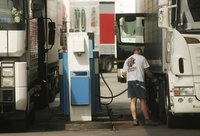 A truck driver pumping gas at a service station.