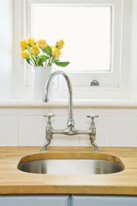 Stainless steel faucets reflect light and add brightness to a kitchen.