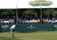 A golfer preparing to putt near a stand filled with fans.
