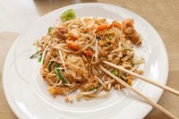 A plate of pad thai with iron-rich components including shrimp, bean sprouts and crushed peanuts.