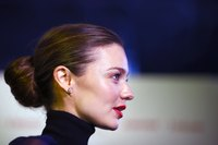 Model Miranda Kerr pairs a navy blue turtleneck with simple diamond studs.