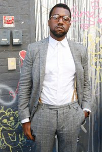 Kanye West creates a look by pairing suspenders with a button-up shirt and eyeglasses.