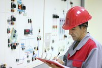 A power plant operator inspects an instrument panel.