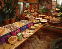 Jazz up your buffet table by adding colorful decorations and multiple layers of food.