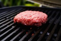 Red meat burger cooking on grill.