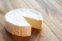 Brie cheese comes in wheels with a white rind.