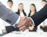 Close-up of company representatives shaking hands in business meeting