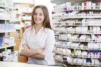 Pharmacist standing in front of a shelf of prescrition medications.