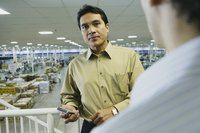 A business man is standing in a manufacturing facility.