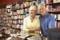 A middle-aged couple posing inside the bookstore they own