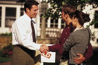 A couple is shaking hands with a real estate agent outside of a listed home.