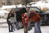 A family unloading gifts from a vehicle at a holiday get together.