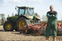 A farmer standing in front of his tractor.