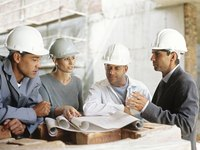 Men and woman having a meeting at a construction site.