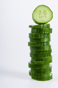 Soak the cucumbers in water before adding to salad to remove some of the water in the cucumber.