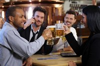 Office workers toasting beers at a pub.