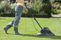 Man using electric lawn mower to cut grass