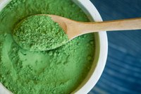 A close-up of a wooden spoon in a bowl of green seaweed powder.