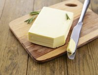 Fresh butter on a cutting board with knife.