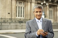 Mature businessman working on phone with charming smile on face.