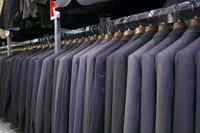 A rack of suits for sale at a shop.