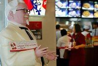 A close-up of an iconic statue of Colonel Sanders inside of a KFC Restaurant.