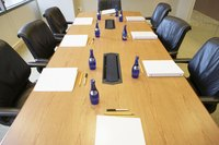 A  high angle view of informational binders on a conference room table.