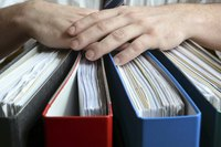 Close-up of hands on top of company's spending binders