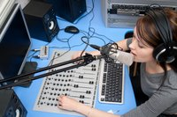 Woman in a radio broadcasting setting.