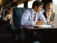 Businessman and businesswoman working on train.