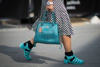Woman wearing blue jelly shoes.