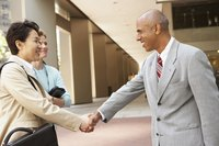 Two business professionals shaking hands outside of an office building.