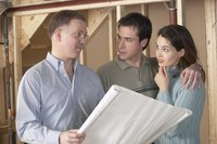 A young couple discusses blueprints with a construction contractor